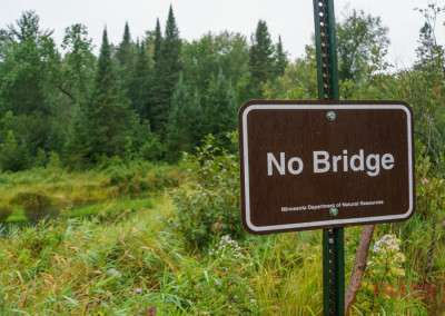 An sign warns hikers there's no bridge ahead on a hiking path