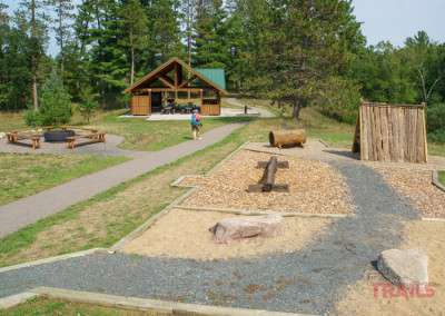 A woman walks a paved path toward a picnic shelter past a playground and fire ring