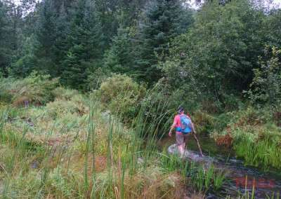 A woman carrying a walking stick walks through a small river in the rain