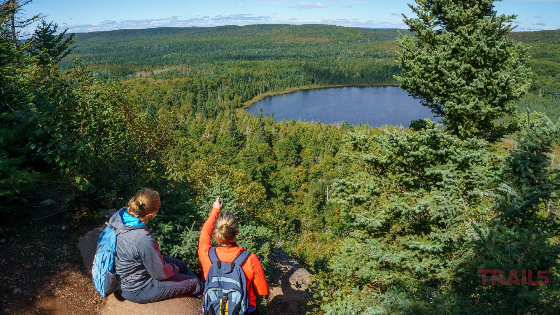Two female hikers enjoy a scenic view at the top of the Oberg Loop on the Superior Hiking Trail in Minnesota
