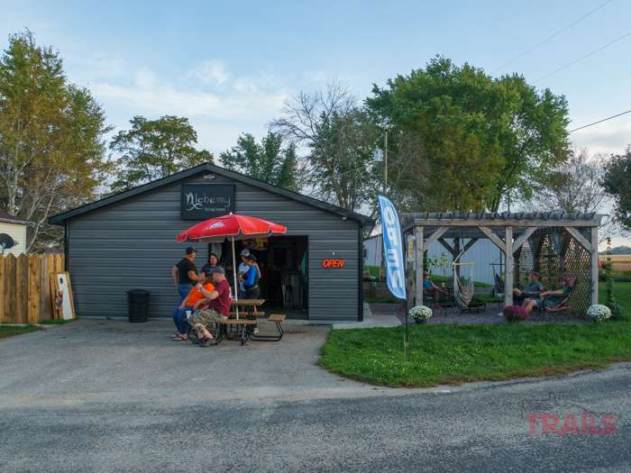 A view of the outside of Alchemy Brewing Company in Leon WI shows patrons sitting at a picnic table outside on a mild evening