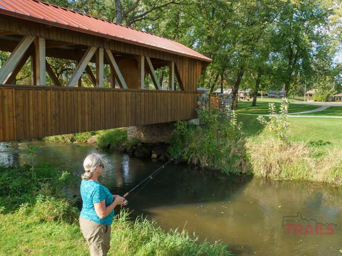 A woman fishes a small stream in a park near a covered wooden bridge
