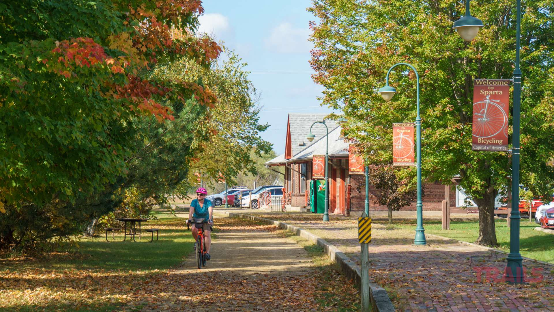 A woman rides her bicycle along a gravel path in the fall with a historic train depot in the background