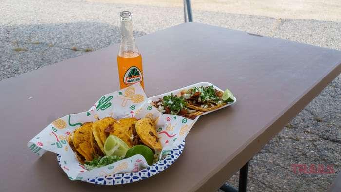 A plate of tacos al pastor and biria tacos with a bottle of Jarritos mandarin soda