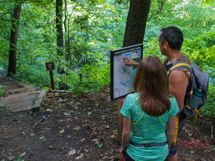 A couple pauses to examine a wayfinding map while hiking the Lower Bluffline Trail at Minnesota's Frontenac State Park