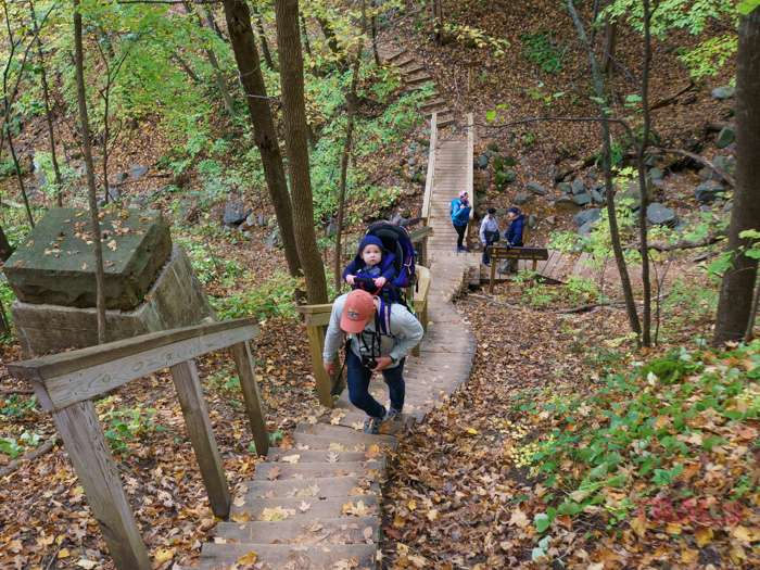 A man carrying an infant in a backpack carrier walks up a steep flight of stairs at Interstate State Park in Taylors Falls, MN