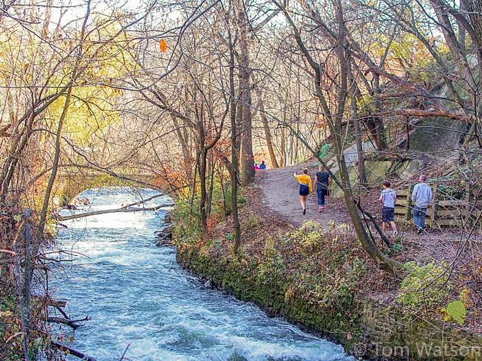 People walk up and down the trails along Minnehaha Creek in Minneapolis on a mild fall day