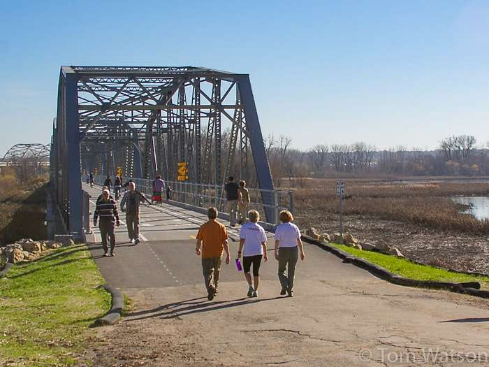 People walk up and down the Old Cedar bridge in Bloomington, MN on a mild fall day