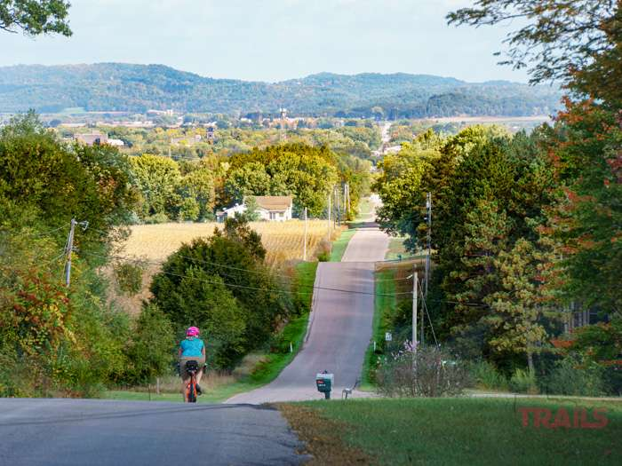 A woman rides a bicycle down a steep hill into a wooded valley in the fall