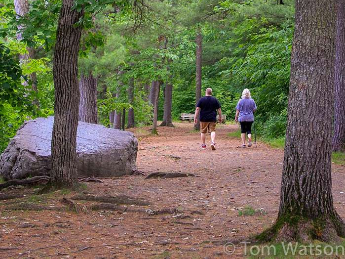 A couple walks the trails past boulders and trees at Minnesota's William O'Brien State Park